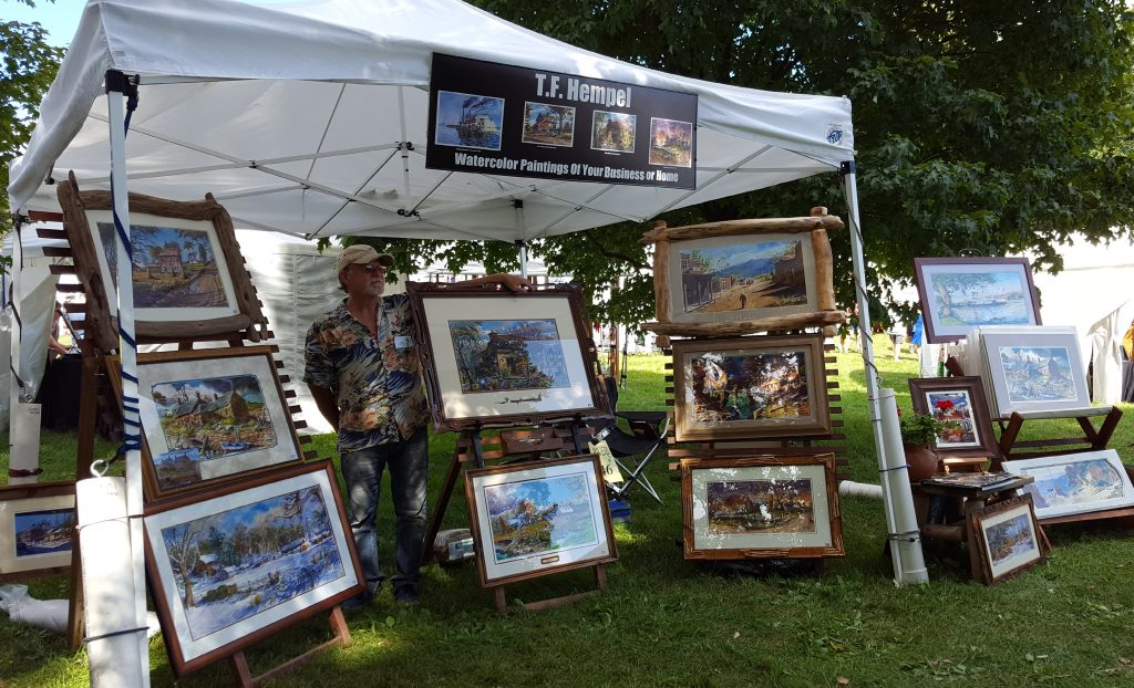 Tom Hempel standing with his paintings at the River Renaissance Festival.